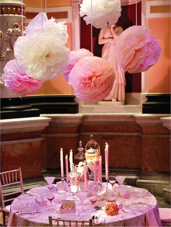 pink and white paper pompoms over the table match the colors and make the space look chic and romantic