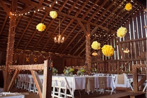yellow paper pompoms and lights on the pillars add a sunshine feel to the barn reception space