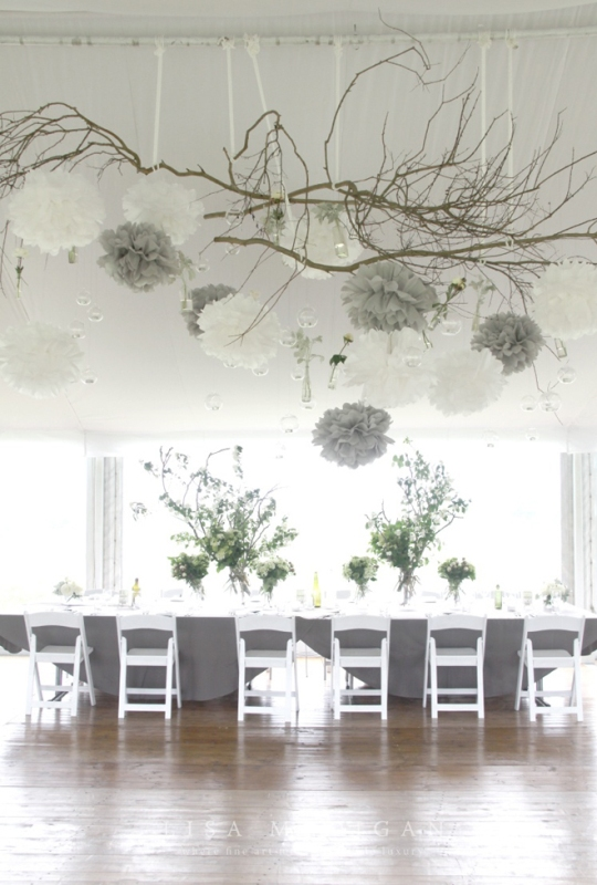 a creative overhead installation of branches, white and grey paper pompoms, crystals, candleholders and white blooms for a winter wedding