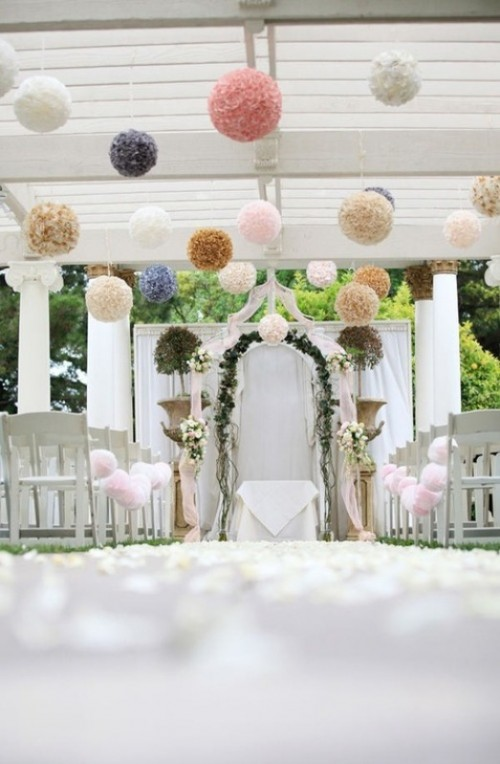 colorful paper pompoms hanging over the ceremony space make it look fun and festive, ideal for a festival-themed wedding