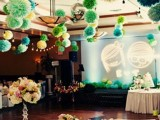 green and yellow paper pompom garlands over the reception space make it look bold and fun