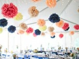 colorful paper pompom garlands over the reception space make it look more fun and add a relaxed feel to it