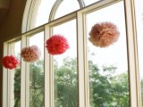 decorate the windows with blush and hot pink paper pompoms hanging on them and make them look fun and bold