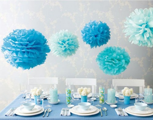 light blue and bold blue paper pompoms over the table accent its blue decor and add an ethereal feel here