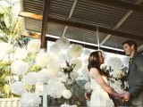 a wedding backdrop of white paper pompoms is a cool decor idea for a modern wedding with a touch of fun