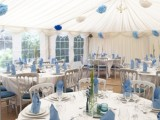 a blue and white wedding reception finished with white chandeliers and with blue, navy and white paper pompoms over the whole space