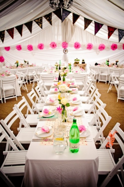 colorful lace paper buntings and hot pink paper pompom garlands make the reception space look bold and fun