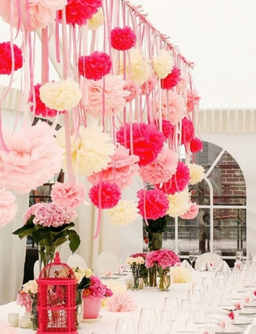 an overhead installation with pink, fuchsia and white paper pompoms and matching pink blooms on the table for a romantic feel