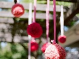 red and pink paper pompoms hanging over the reception look festive, bright and fun and add color to the space