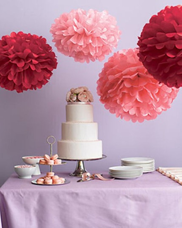 oversized red and pink paper pompoms over the dessert table look very cool, fresh and bold