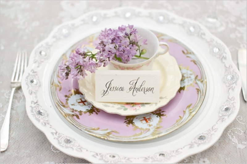 a beautiful lilac place setting with floral print plates and a charger plus a teacup with lilac inside