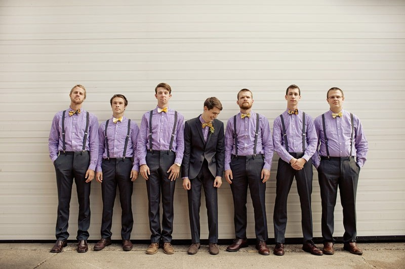groomsmen wearing lilac shirts and black pants and bow ties to look super cool and chic