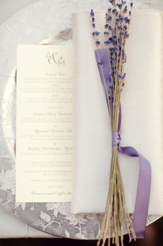 a silver floral print charger, a menu, a napkin and some lavender with lilac ribbon for a chic place setting
