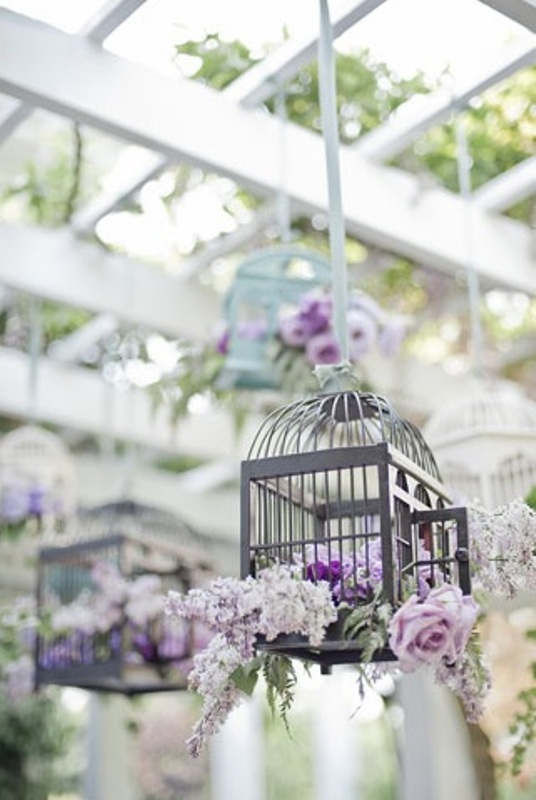 suspended cages with pink and lilac blooms and pale greenery can be amazing for a vintage wedding