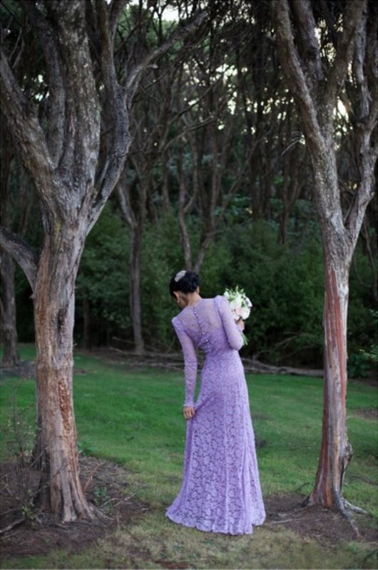 a fitting lilac lace wedding dress with long sleeves, buttons on the back and a high neckline