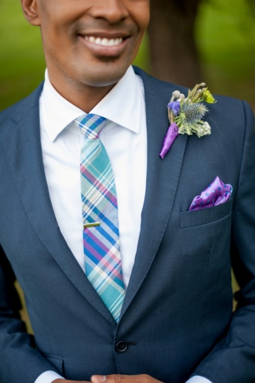 a bold blue, purple and mint printed tie, a purple pocket square and a green boutonniere with a purple wrap