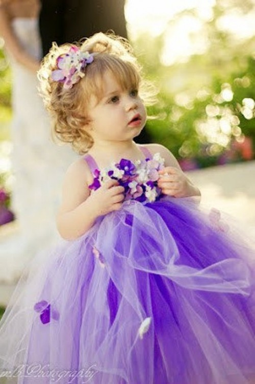 a purple flower girl dress of tulle and with a floral bodice plus a purple floral crown is super cute and bright