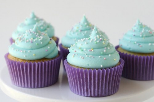 cupcakes with mint and sprinkle icing and purple liners are delicious and cool-looking