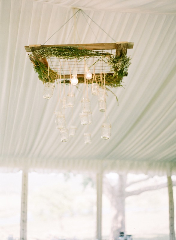 a unique woodland wedding chandelier of a wooden frame, greenery and hanging bulbs and jars