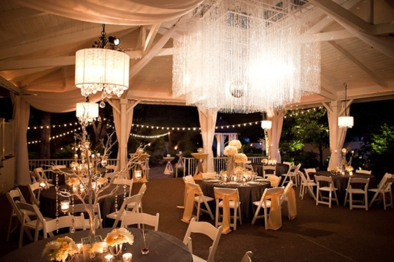 white chandeliers with crystals hanging down from lampshades and an oversizedsquare crystal chandelier as a centerpiece