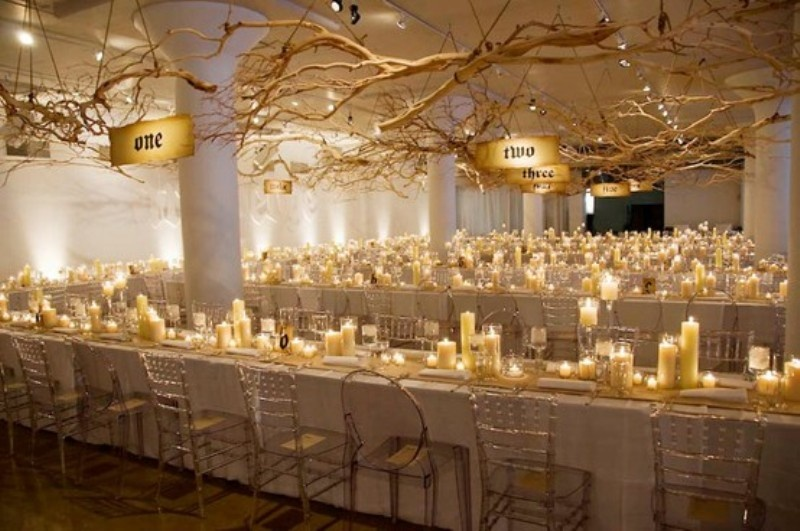 plenty of candles on each table and branches with lights make the space welcoming and cozy