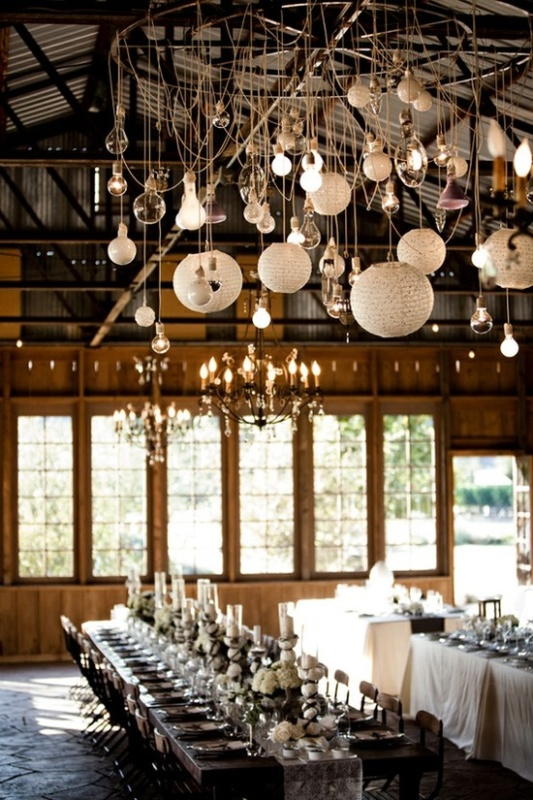 a creative chandelier with various bulbs hanging and paper lamps and vintage chandeliers light up the space in a cool way