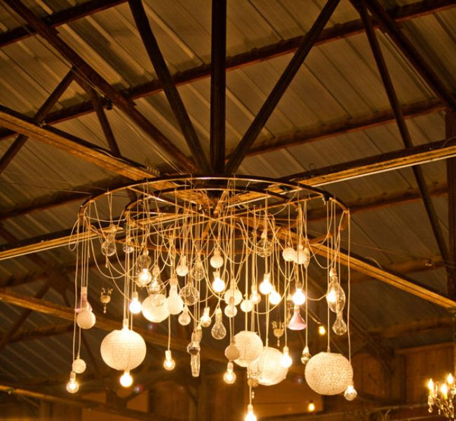 a whimsical chandelier with lots of various bulbs is a cool decoration and a lighting piece for a rustic venue