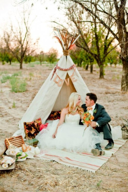 a romantic wedding picnic with a boho teepee, bright pillows, blooms, layered blankets for a boho-loving couple