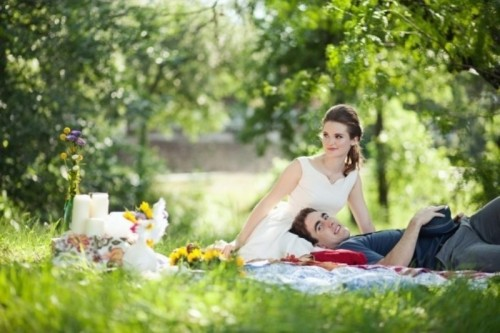 a simple and cute wedding picnic with colorful blankets, candles and bright blooms for a summer celebration