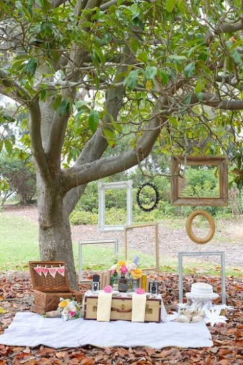 a vintage wedding picnic with a white blanket, with bright blooms, a basket and a vintage suitcase, a wedding cake and empty frames on the tree