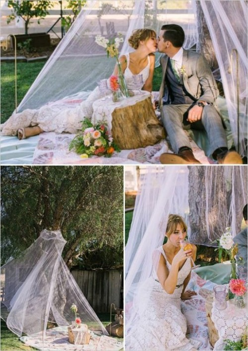 a simple wedding picnic with an airy teepee, a neutral blanket, a tree stump and bright blooms for a spring or summer wedding