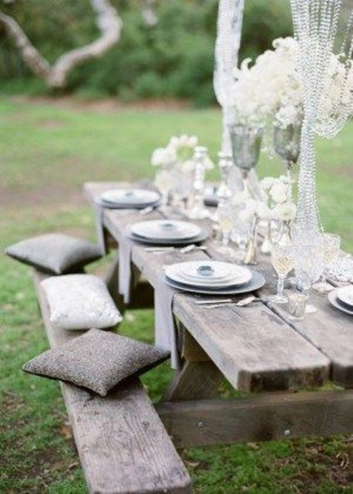 a neutral wedding picnic with a low reclaimed wood table, grey pillows, chargers, white feathers and crystal arrangements