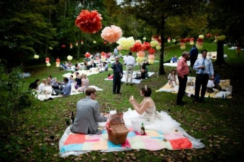 a bright wedding picnic with colorful layered blankets, bright paper pompoms and balloons and picnic baskets with food