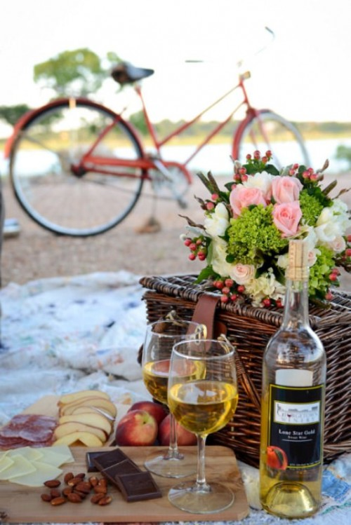 a wedding picnic with a basket, pastel blooms and greenery, apples, cheese, nuts and wine is perfect