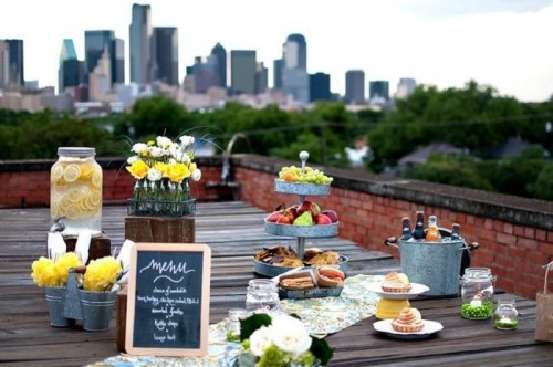 a rustic roof top wedding picnic with a reclaimed wooden table, bright blooms, fruits, lemonade, sweets and candles