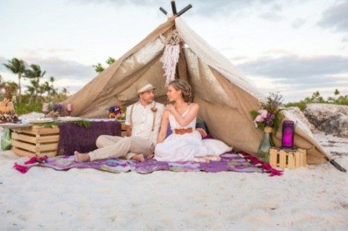 a beach wedding picnic with a teepee, colorful blooms, bright glass lanterns, a colorful blanket and pallets as stands