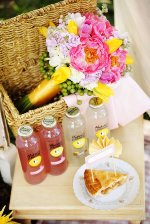 a low picnic table with food, refreshing drinks and a small basket with bright blooms inside