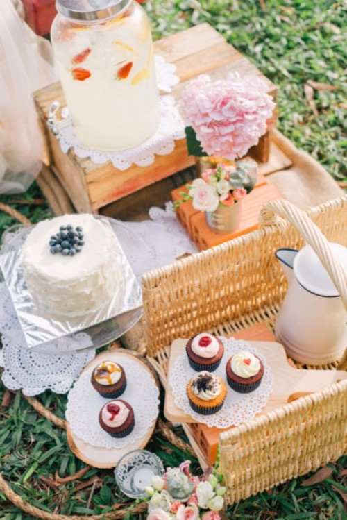 a rustic summer wedding picnic setting with crates, baskets, bright blooms, delicious sweets, lemonade and tea and coffee