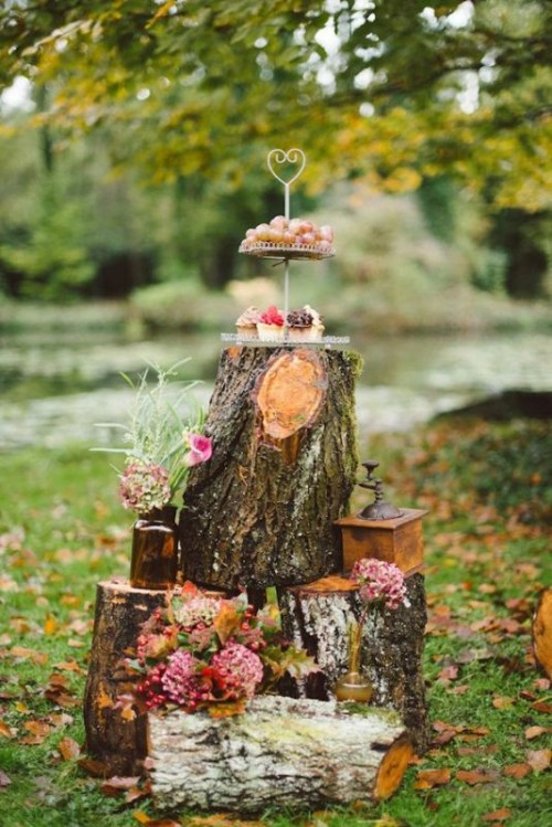 a rustic or woodland dessert display of tree stumps, bright blooms and greenery and desserts on a stand on top