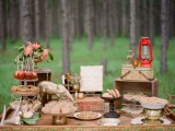 a rustic woodland dessert display decorated with antlers, blooms, greenery, gilded animals and crates as stands