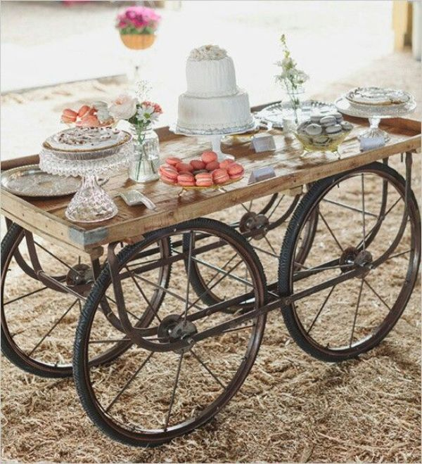 a vintage rustic dessert cart decorated with blooms in jars and styled with crystal cake and dessert stands