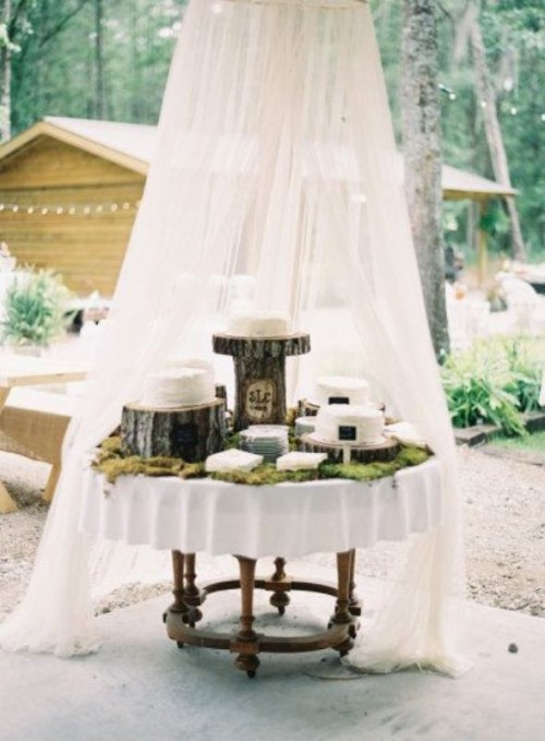a rustic dessert display with moss on it and tree stumps and stands with a curtain over it is a cool idea