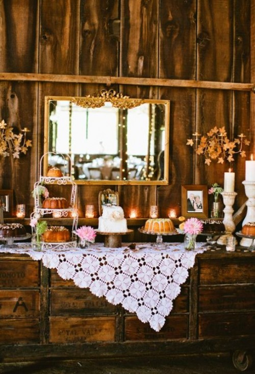 a vintage rustic dessert table made of rough wooden crates, with a doily tablecloth, candles and a vintage mirror in front of it