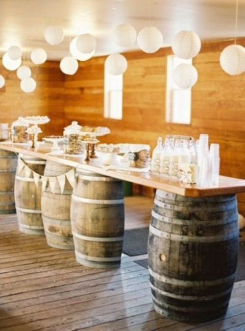 a rustic dessert and drink display of wine barrels and a tabletop on them, various sweets and milk bottles