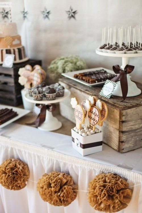 a rustic vintage dessert display of a table with crates and vintage white stands for food plus a bunting with fabric flowers
