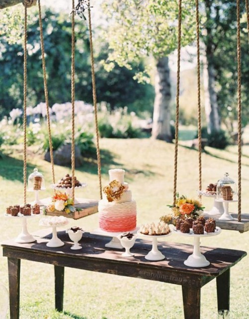 a rustic dessert display of a wooden table with stands and bright blooms and a couple of swings over it is creative and cool
