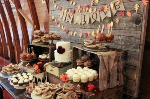 a rustic dessert table with lots of wooden stands and crates, a burlap bunting and a colorful leaf bunting and lots of tasty sweets