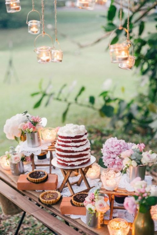 a rustic dessert table of a wooden table, some wooden stands and holders, pastel blooms in vases and candles in candleholders