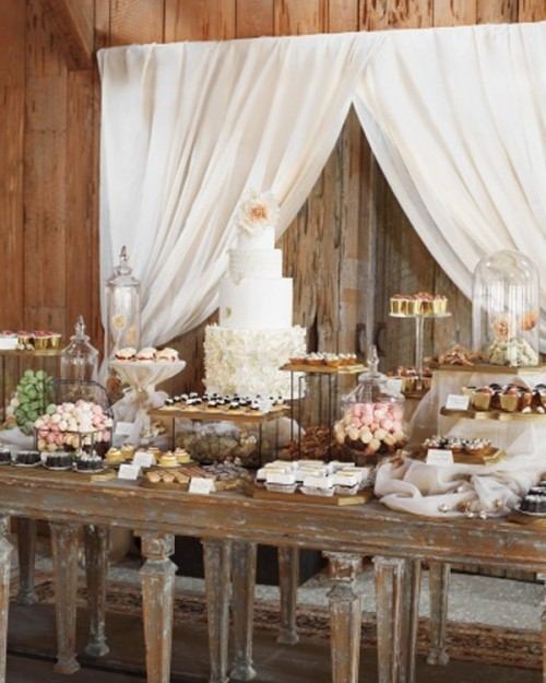 a rustic food display of a shabby chic table, vintage stands and cloches with sweets and some curtains behind the table