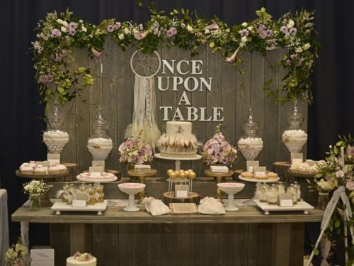 a refined rustic dessert table of a wooden table and a wooden screen with greenery and a dream catcher, some pastel and neutral blooms and stands and glass jars with sweets
